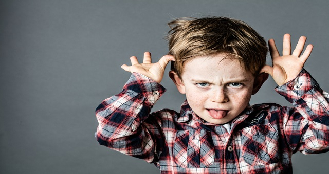 civility, incivility, angry little brat enjoying making a grimace, sticking out his tongue, playing with his hands for misbehavior, contrast effects, grey background